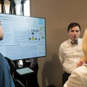 James Pennington, SDM '18, discusses his team's poster at the Technology Showcase with fellow students.