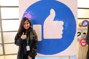 "Afra Ansaria gives a thumbs-up in front of a giant Facebook ""Like"" button"