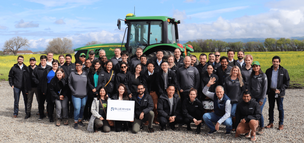 Students and Blue River staff in front of a tractor in an open field