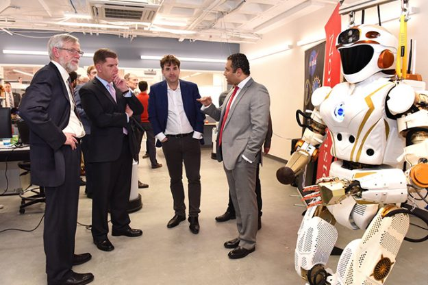 Fady Saad speaks with a group of men next to a humanoid robot