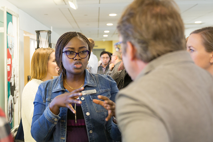 A Black woman wearing a denim jacket and glasses explains a concept to a man at a poster session.
