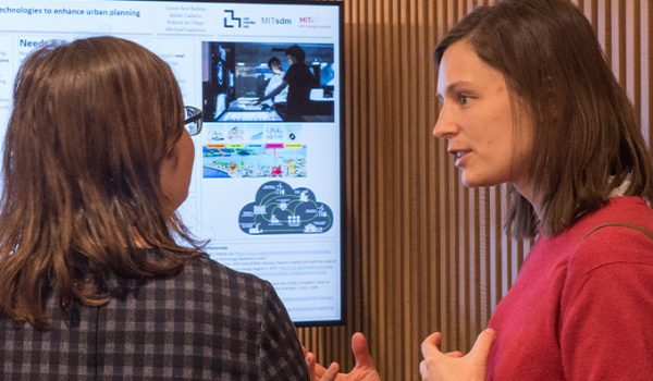 A woman in a red sweater explains a concept to another woman as they stand in front of a monitor displaying a poster