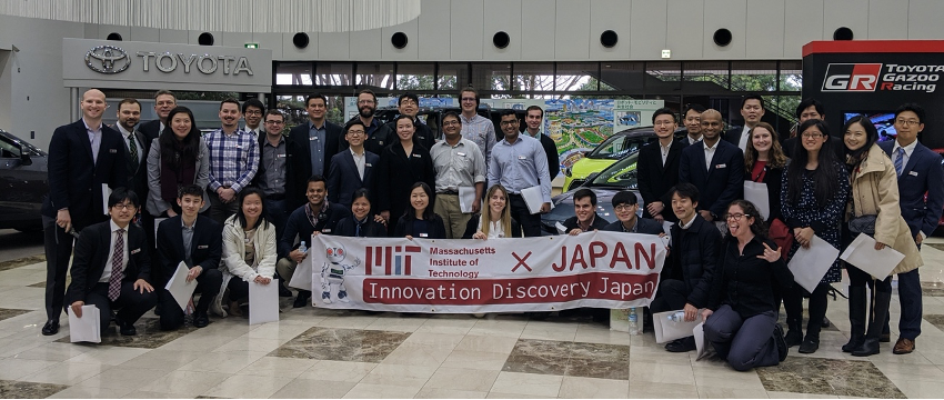 Students stand in a showroom at the Toyota Kaikan Museum holding the MIT IDJ banner.
