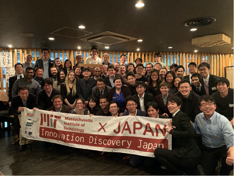 A large crowd of students, staff, and others gather behind the IDJ banner in a bar