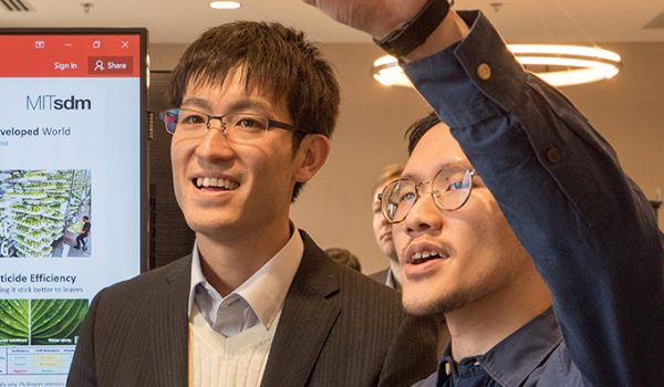 Two students look at a poster, one raising his arm to point at a part of it.