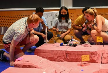Students gather around a Lego rover, which is navigating a model of the Martian landscape